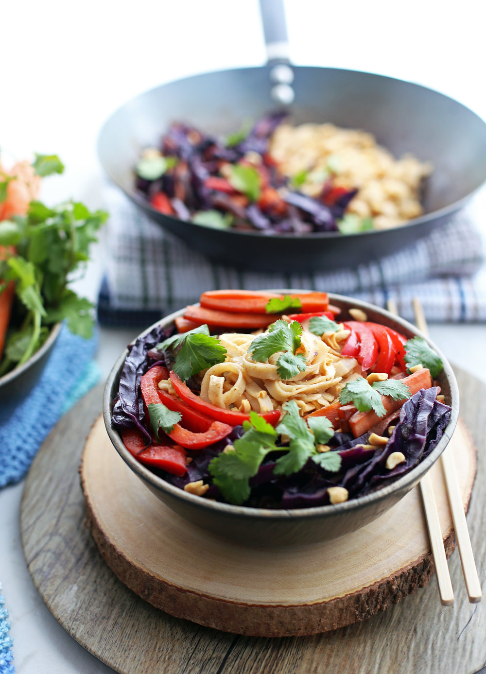 Stir-Fry Vegetables and Noodles with Peanut Sauce in a wooden bowl and in a wok behind it.