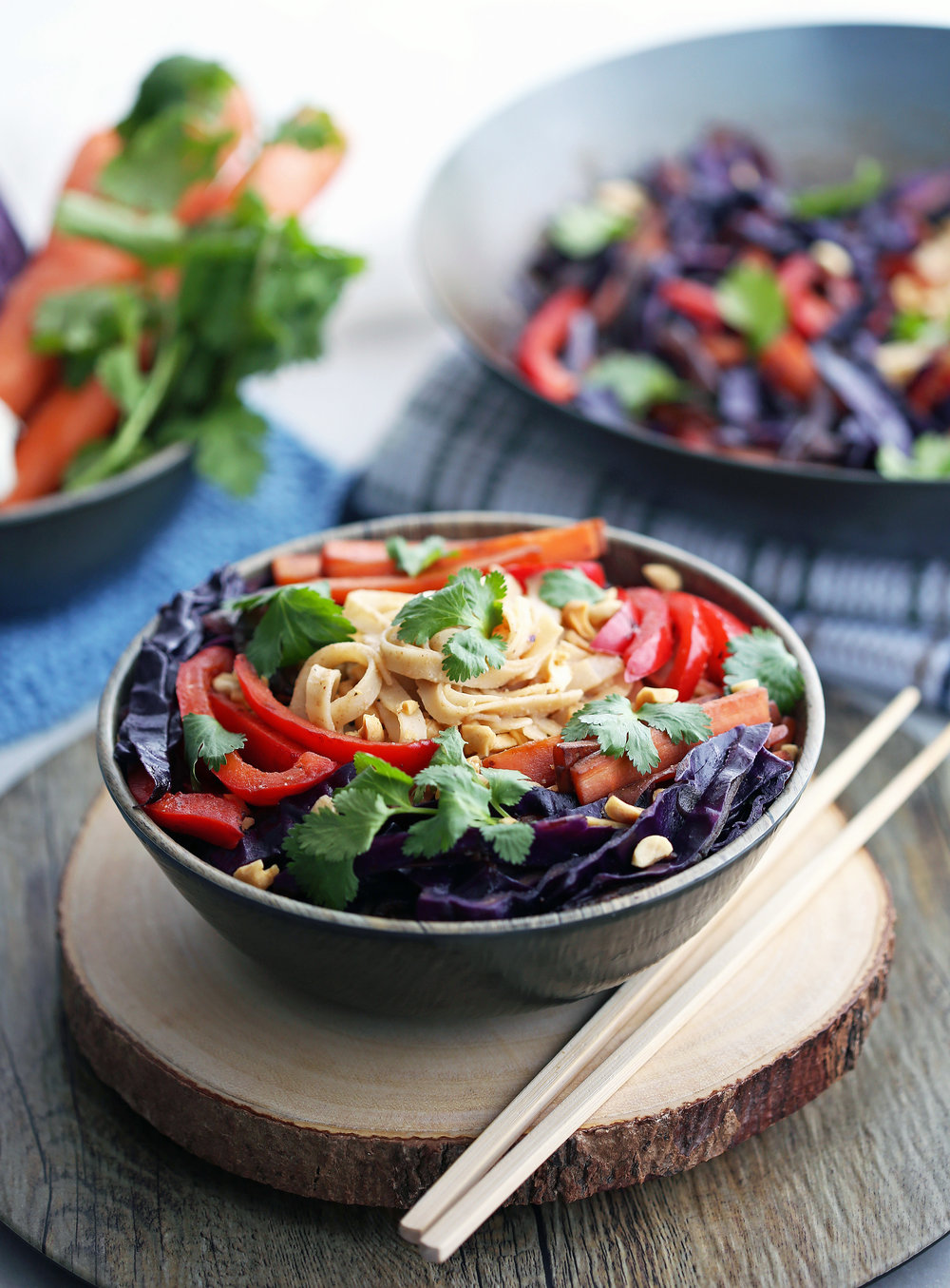 Colourful Stir-Fry Vegetables and Noodles with Peanut Sauce in a wooden bowl.