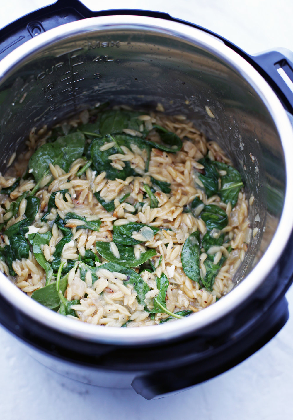 Cooked lemon pepper orzo with feta and spinach in an Instant Pot.