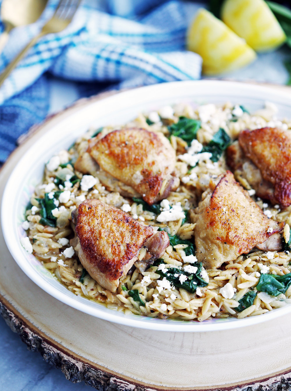 Crispy skin chicken thighs and lemon pepper orzo with feta and spinach on a large oval platter.