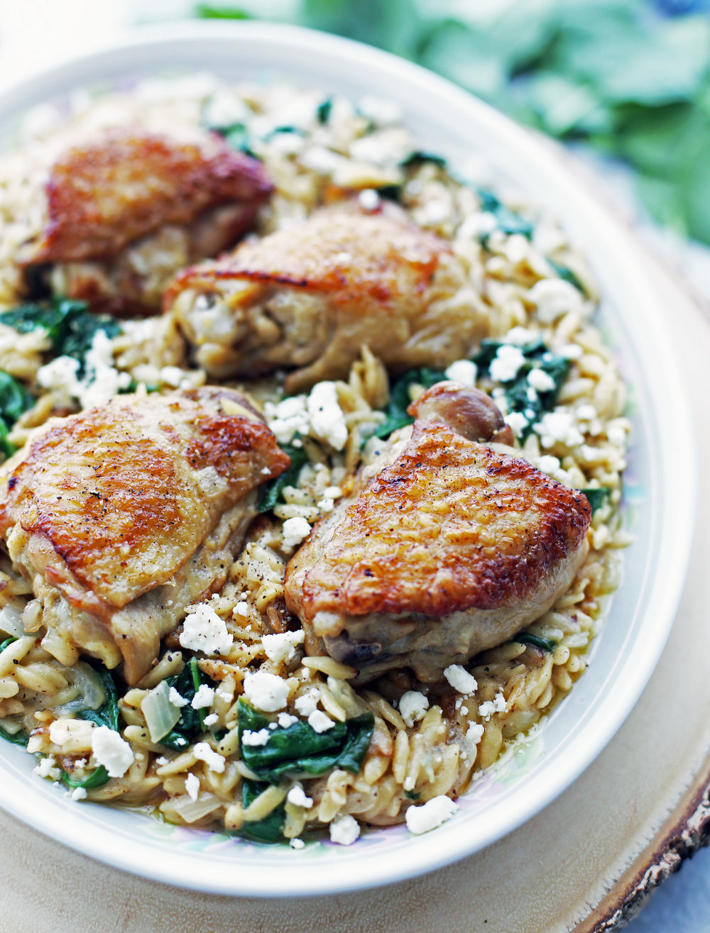 Instant Pot Lemon Pepper Orzo with feta cheese and spinach and chicken thighs on a large oval platter.