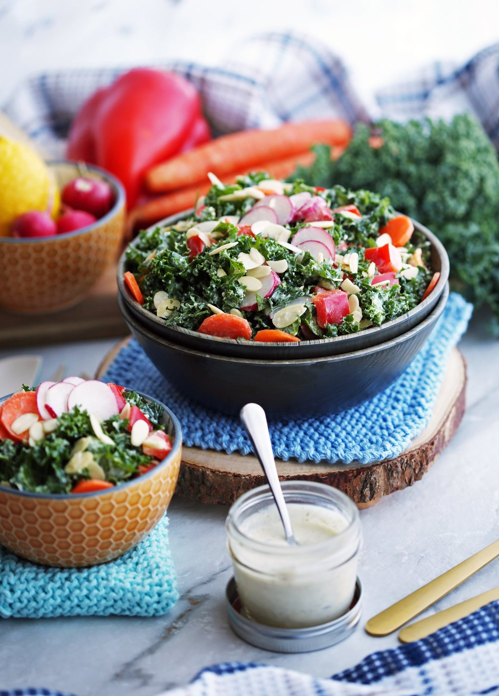 Crunchy Kale, Carrot, Pepper, and Radish Salad with Creamy Parmesan Yogurt Dressing in a wooden bowl and in a small orange bowl.