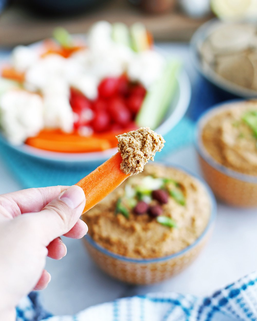 Close-up view of a hand holding a carrot stick that has been dipped in spicy roasted cauliflower garlic dip.