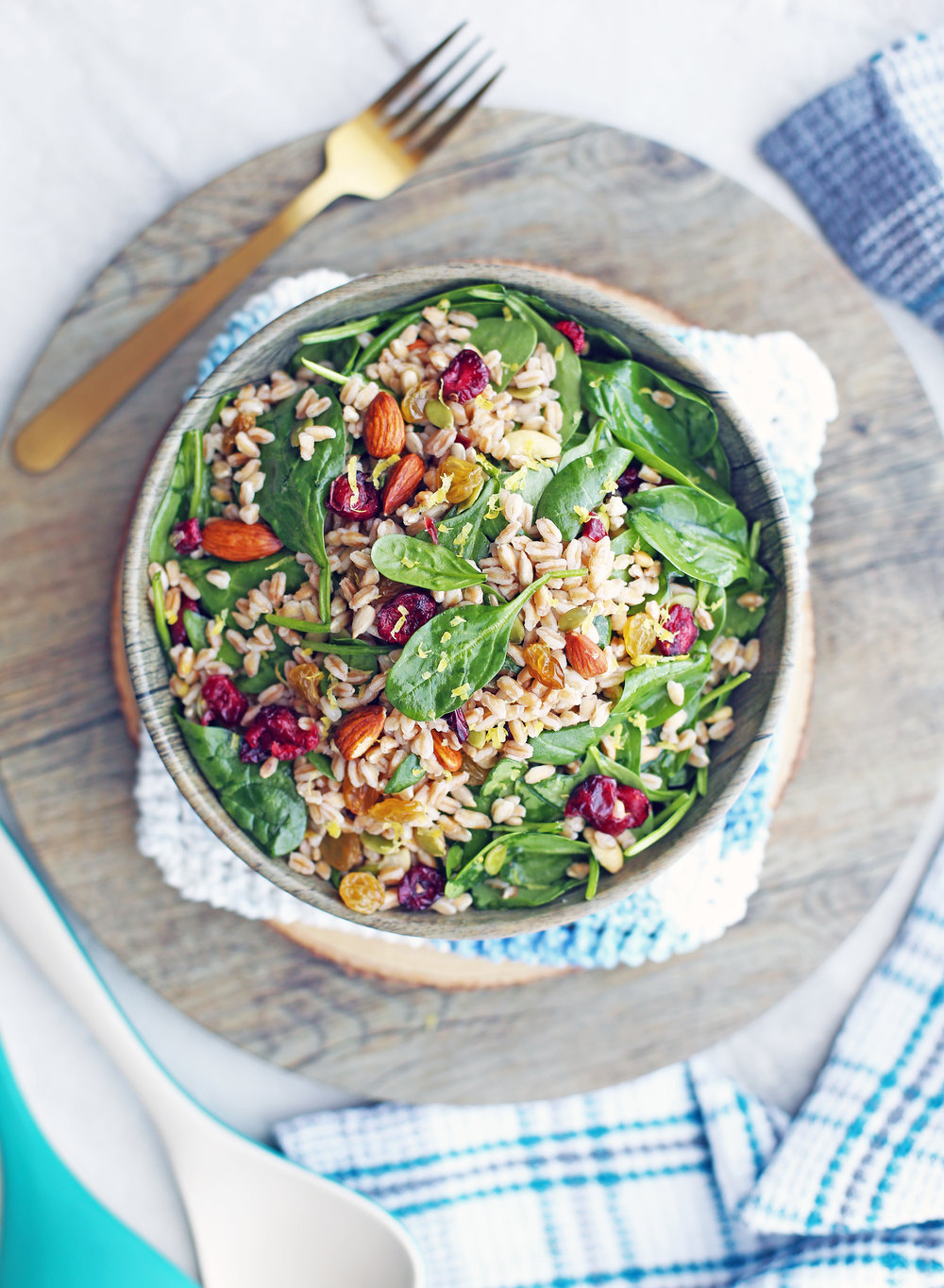 Overhead view of a salad containing farro, baby spinach, dried fruit, nuts, and seeds in a wooden bowl.