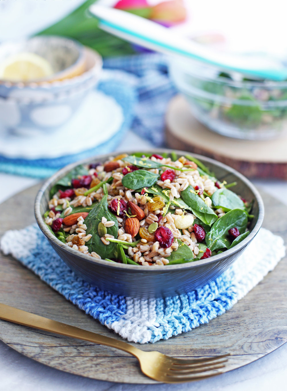 Farro and Spinach Salad with Dried Fruit and Nuts in a wooden bowl; fork in front of the bowl.