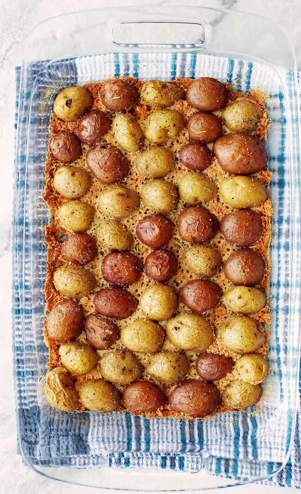 Baked Crispy Parmesan Crusted Baby Potatoes in a single layer in a glass casserole dish.