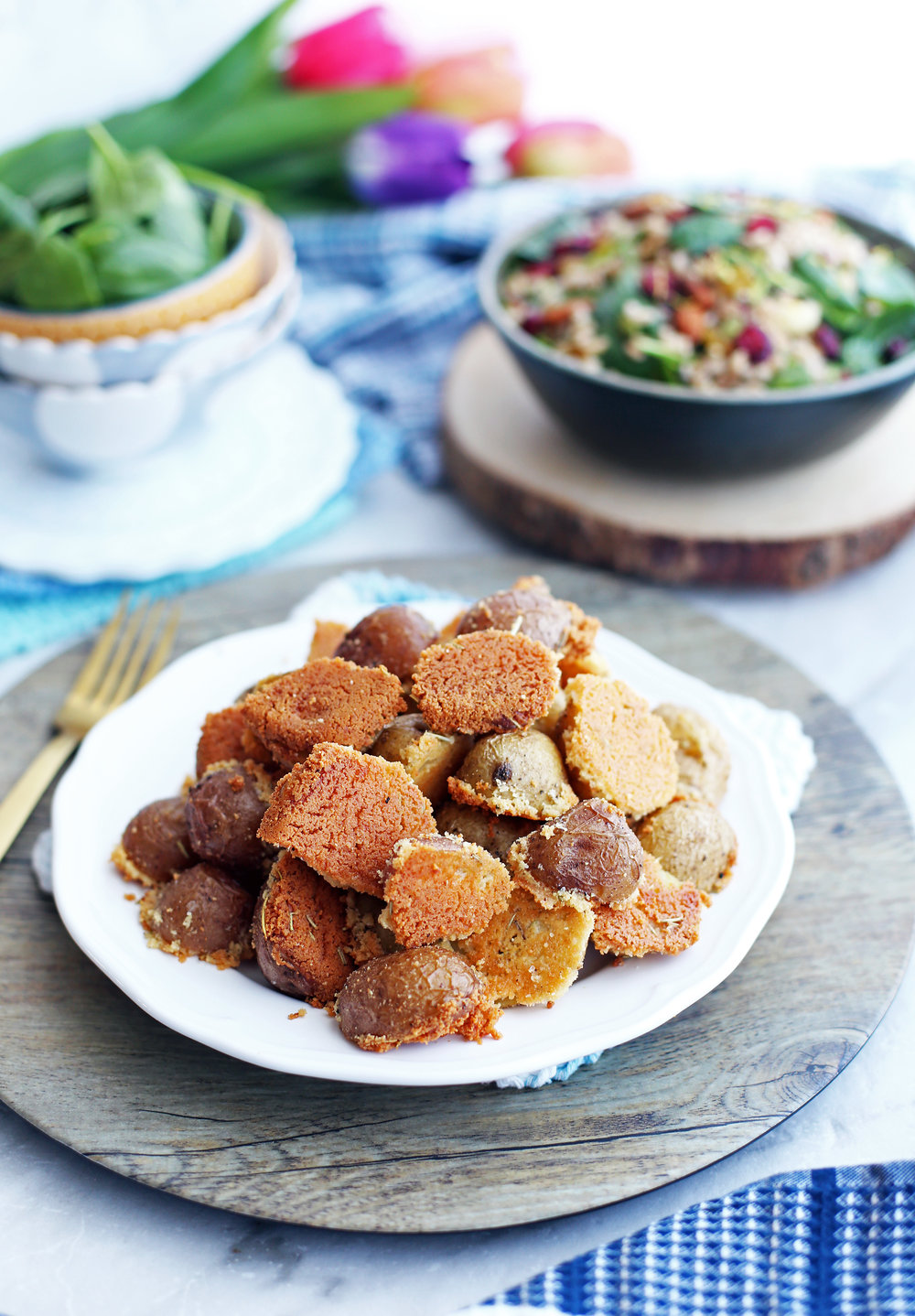 Crispy Parmesan Crusted Baby Potatoes piled on a white plate; a salad in a bowl behind it.