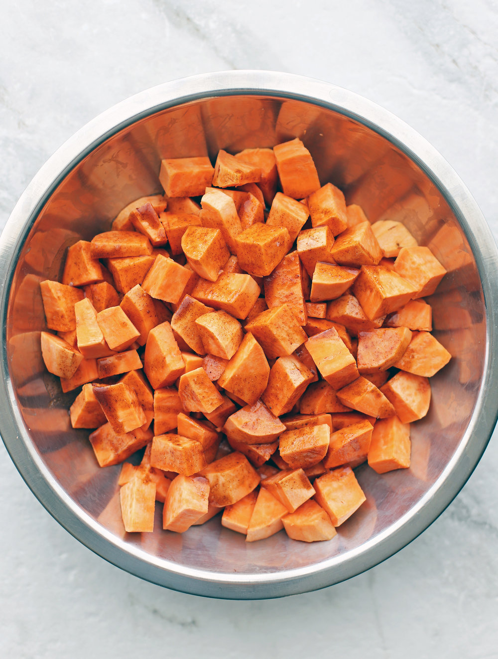 A bowl containing chunks of sweet potatoes, coconut oil, spices, and vanilla extract.