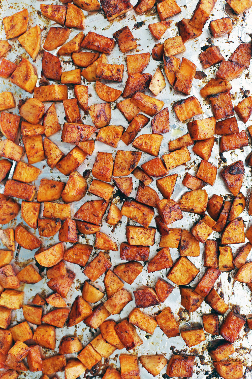 Roasted maple cinnamon sweet potato pieces in a single layer on a baking sheet.