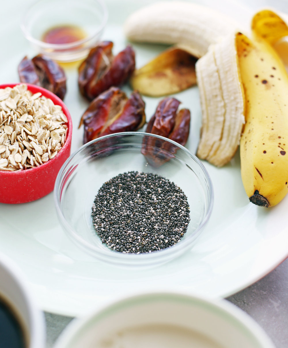 A closeup of a small bowl containing chia seeds; dates, banana, rolled oats, and vanilla extract in the background.
