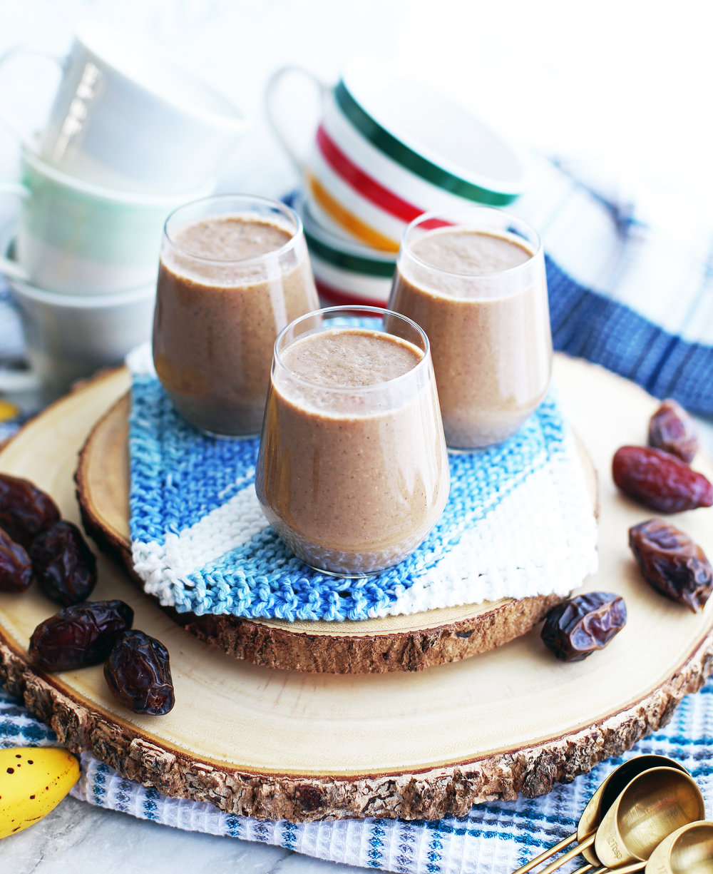 Three glasses of creamy date coffee breakfast smoothies on a wooden platter surrounded by medjool dates and coffee mugs.