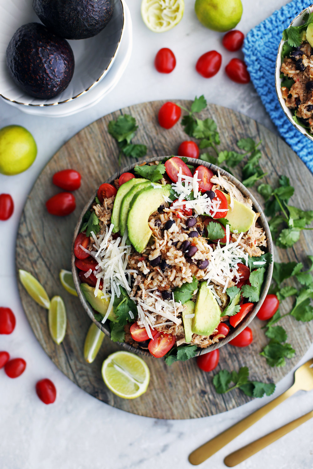 Quick and easy Instant Pot Chicken and Rice Burrito Bowls topped with tomatoes, avocado, cheese, and cilantro.