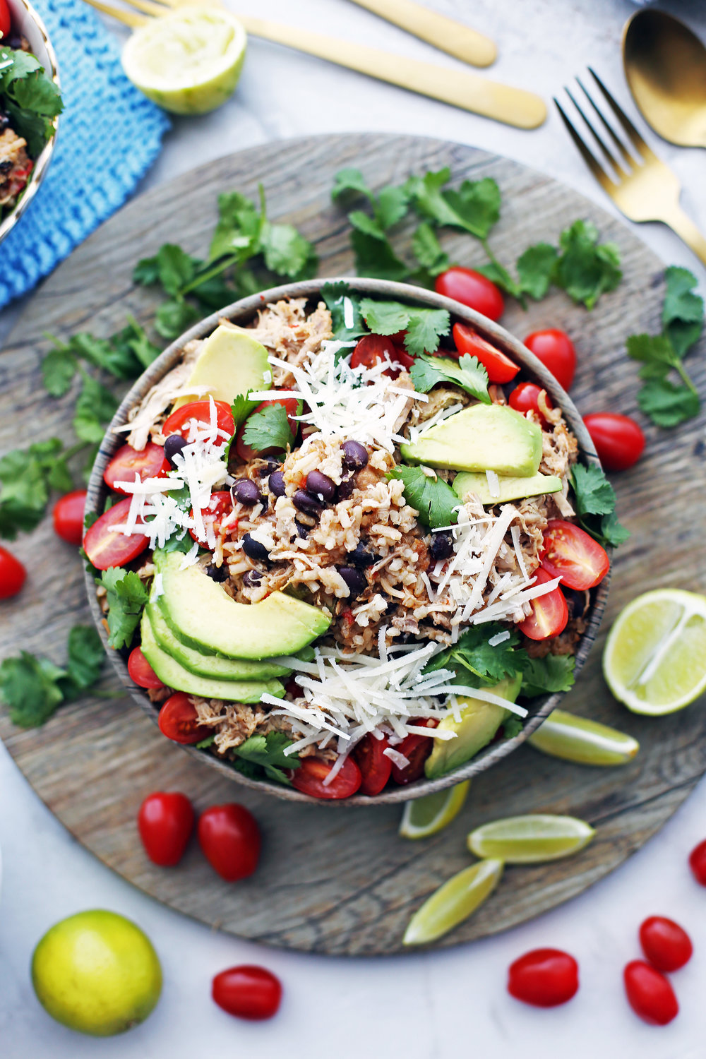Overhead view of a bowl of instant pot chicken, black bean, and rice topped with avocado, tomatoes, cheese, and cilantro.