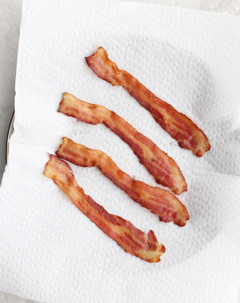 Four crispy strips of bacon on a white paper towel.