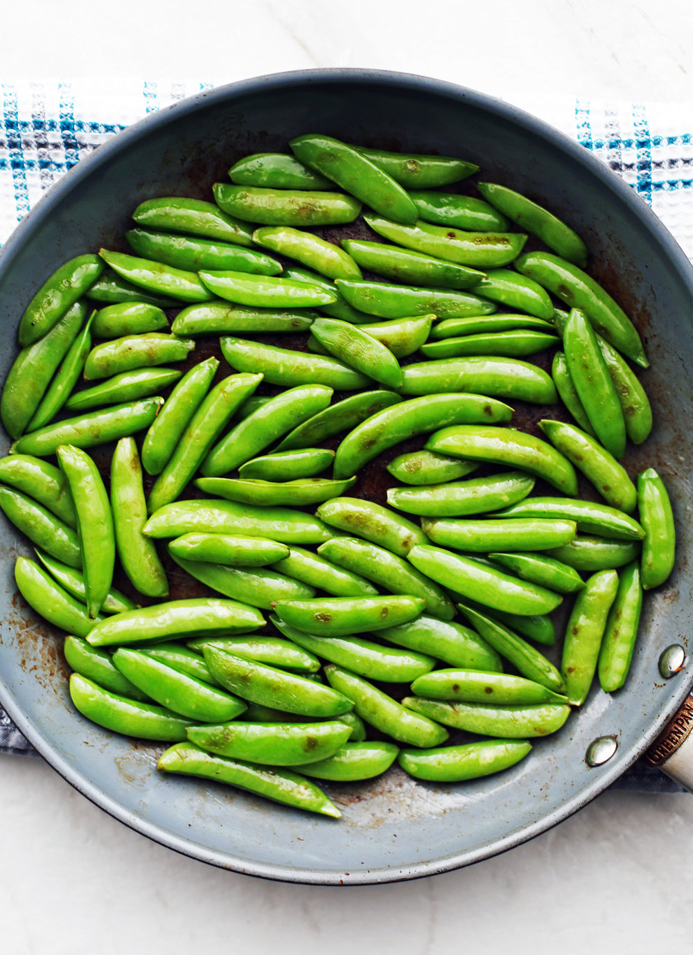 Sauteed sugar snap peas in a blue frying pan.