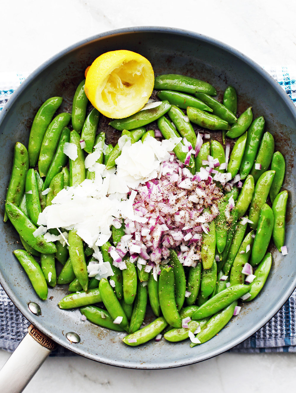 Sauteed sugar snap peas topped with parmesan, red onions, and black pepper in a large frying pan.