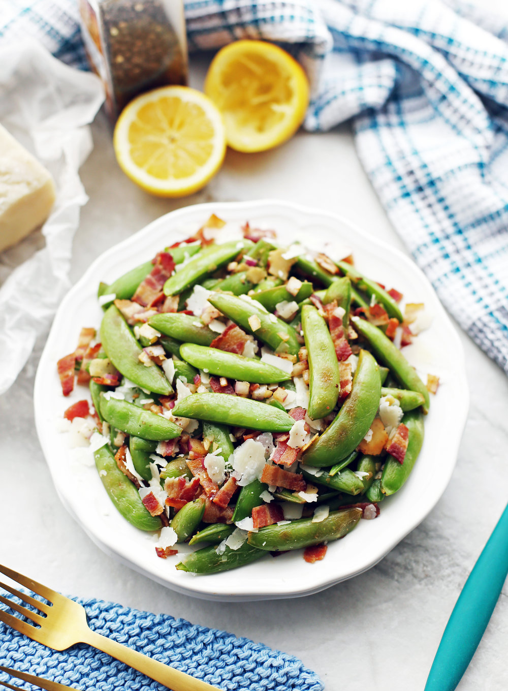 Sugar snap peas with bacon and parmesan piled on a white plate.