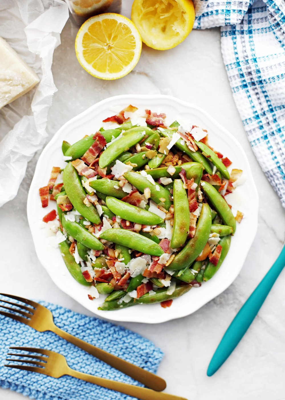 Sugar snap peas with bacon and parmesan on a white plate.