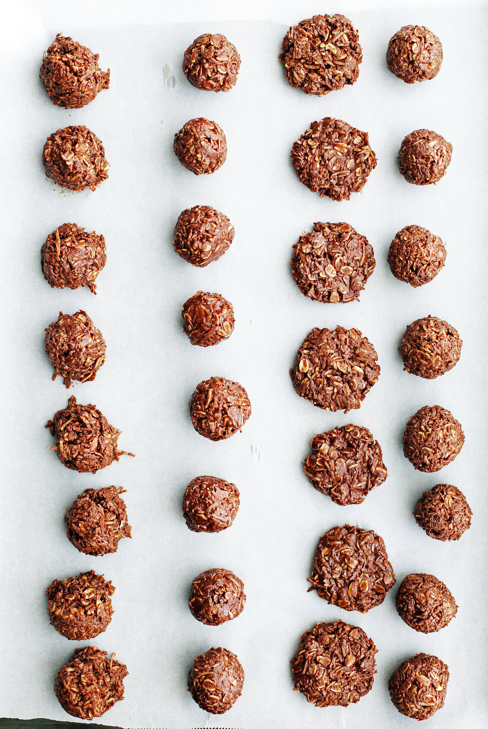 No-Bake Peanut Butter Chocolate Coconut Cookies in rows on parchment paper.