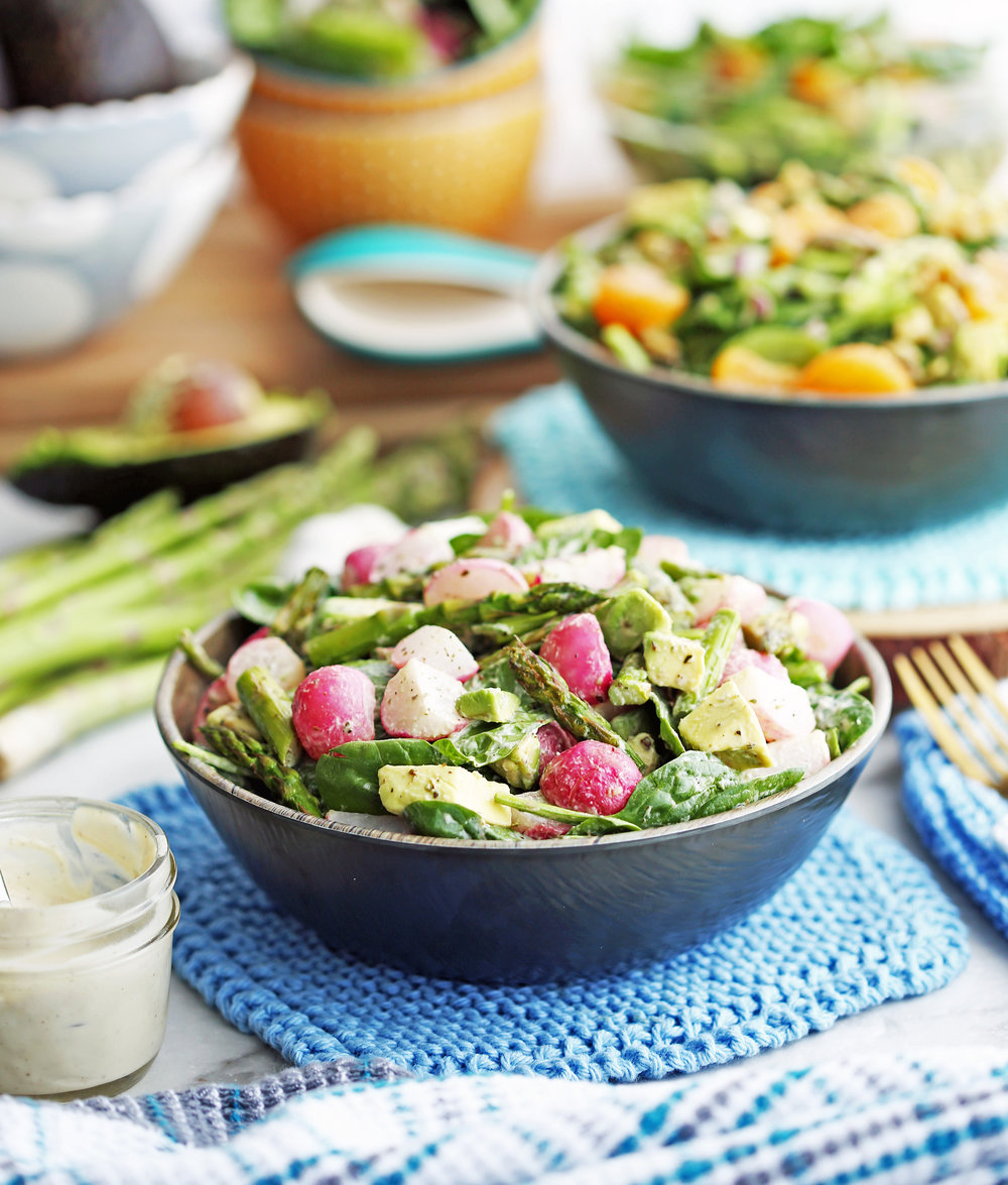 Roasted Asparagus and Radish Salad with Creamy Garlic Cashew Dressing in a wooden bowl with more dressing to its side.