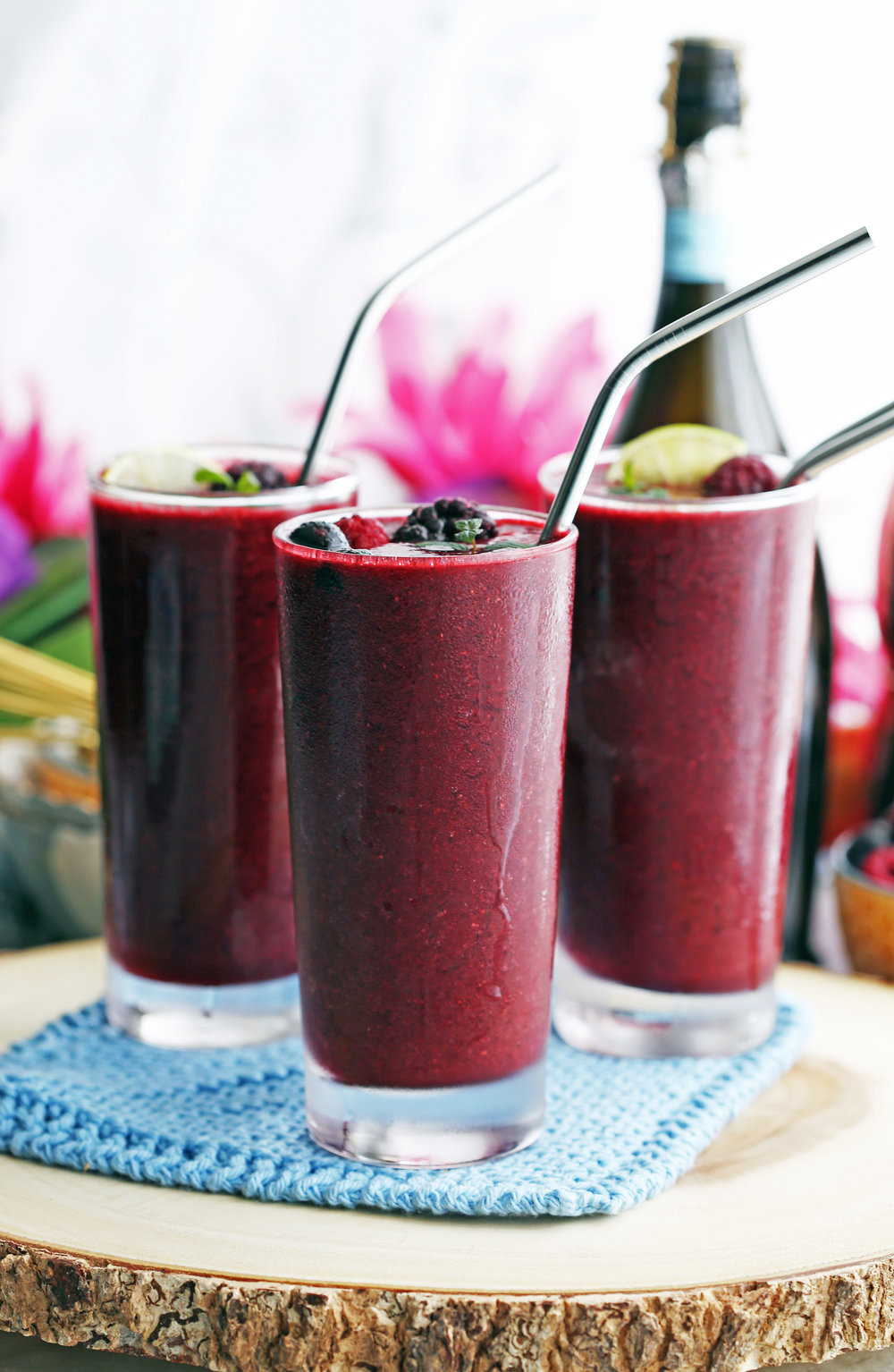 Mixed Berry Prosecco Wine Slushy drinks in three glasses with straws and topped with more berries, lime wedges, and mint.