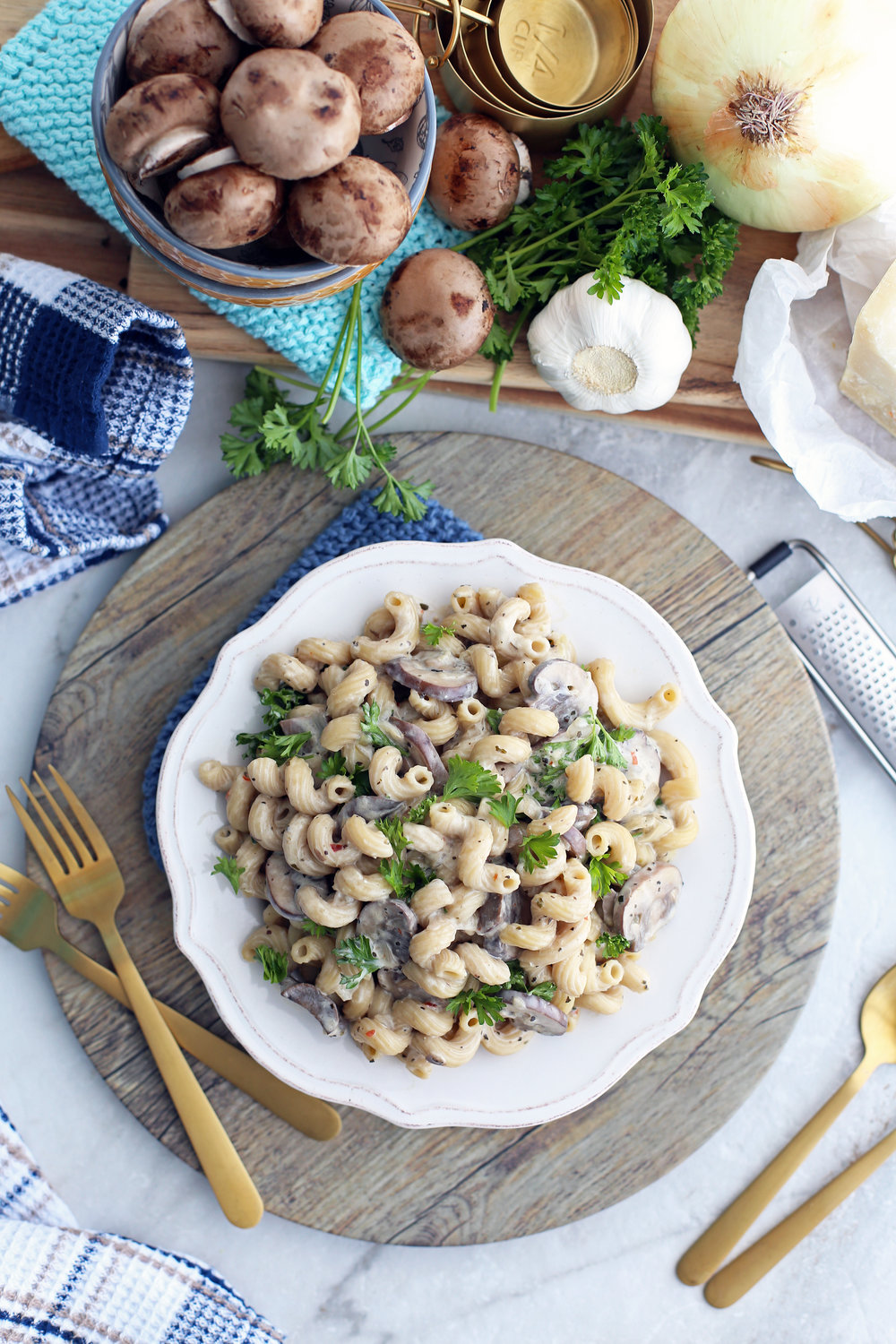Overhead view of a white bowl containing mushroom pasta with creamy parmesan sauce.