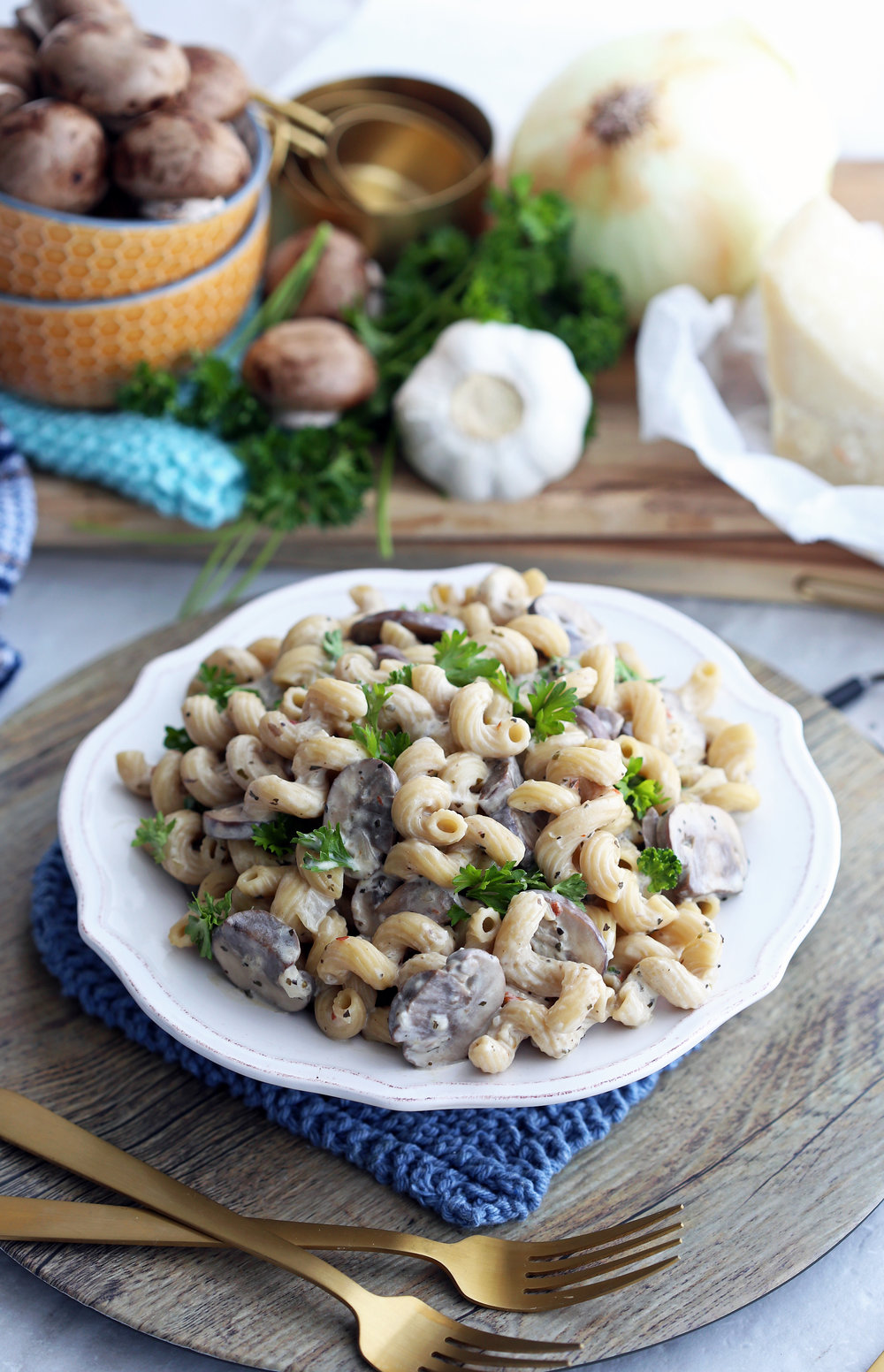 Cavatappi pasta with mushrooms, creamy parmesan sauce, and fresh parsley in a white pasta bowl.