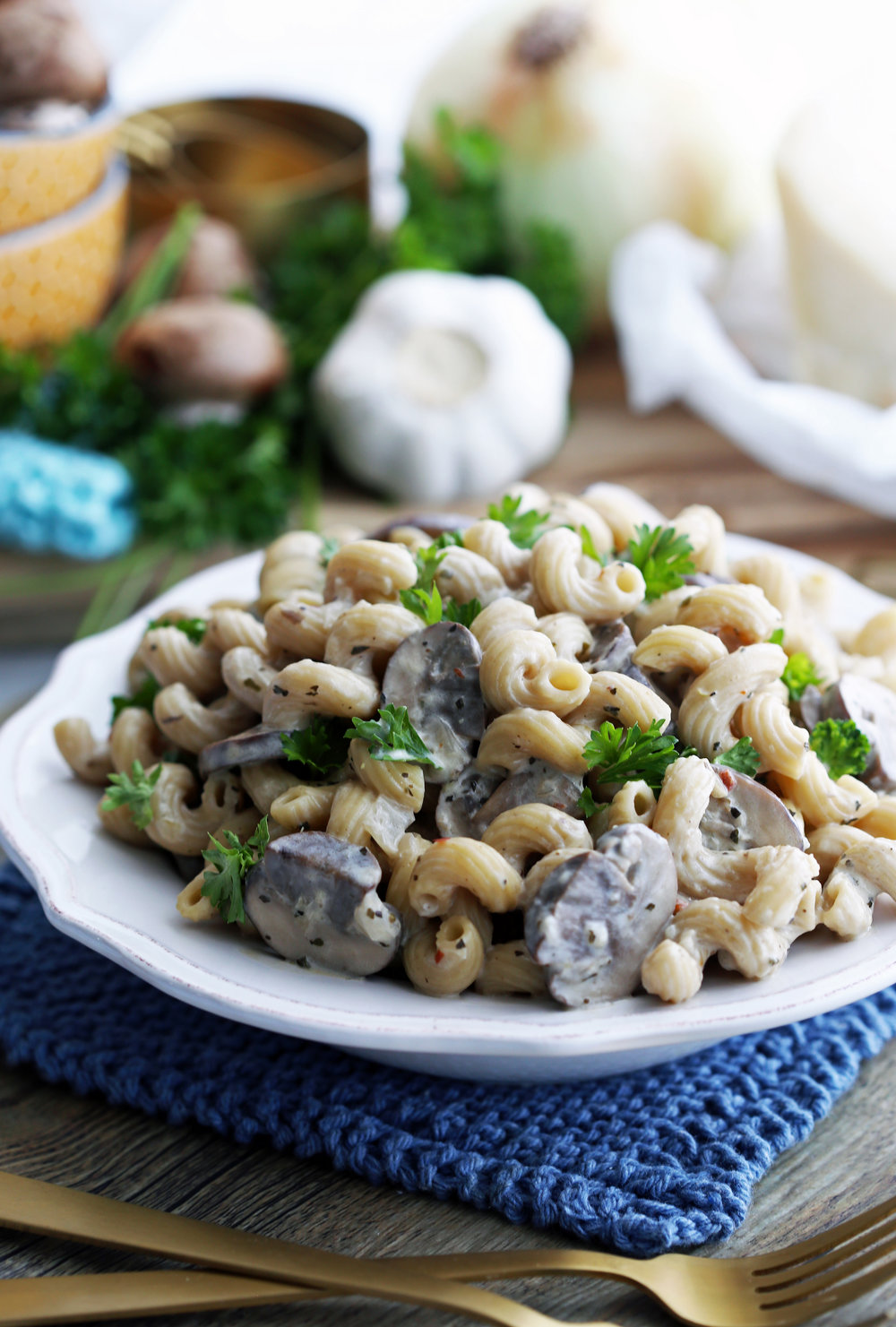 Close-up side view of mushroom pasta with creamy parmesan sauce in a white pasta bowl.