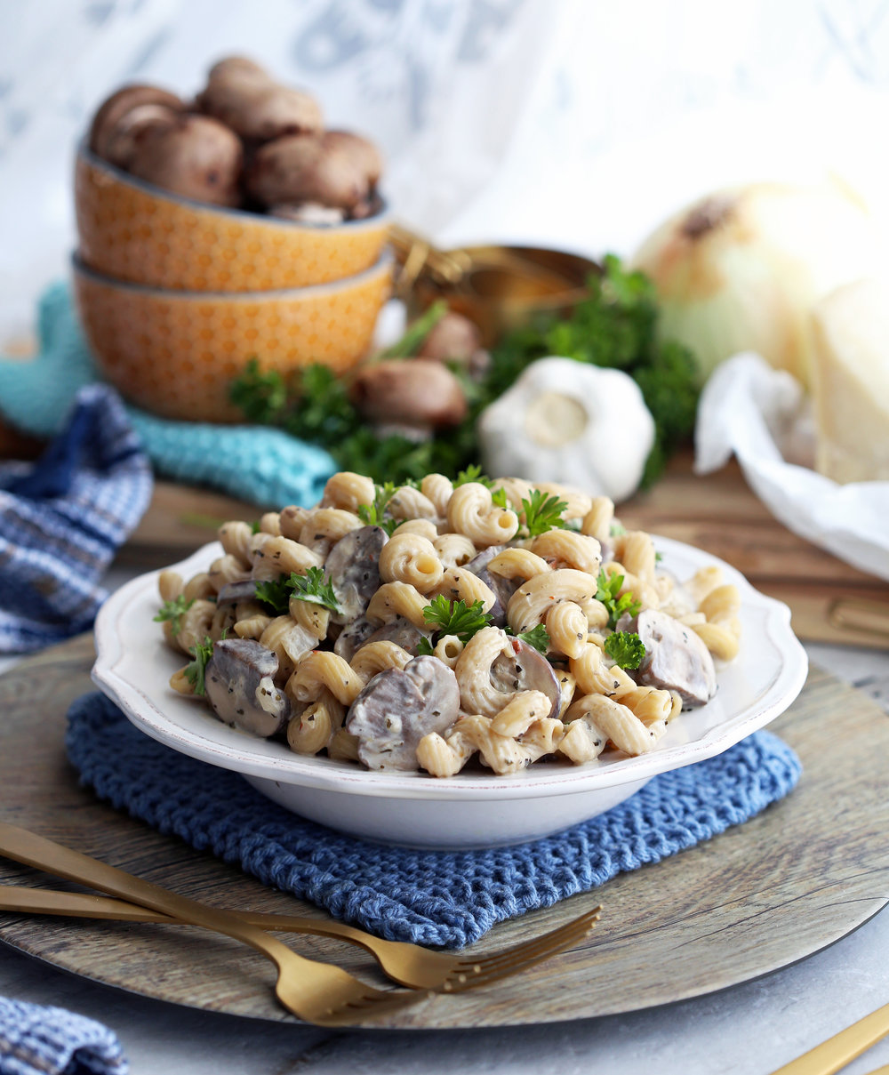 Cavatappi pasta and cremini mushrooms in a creamy parmesan sauce that's garnished with fresh parsley in a white pasta bowl.