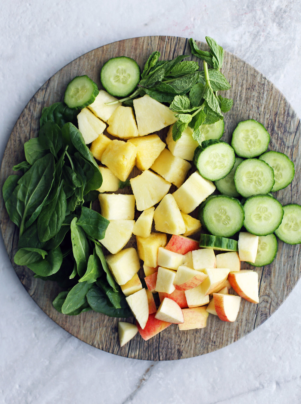 A large wooden platter contained chopped pineapples, apples, cucumber, mint and baby spinach.