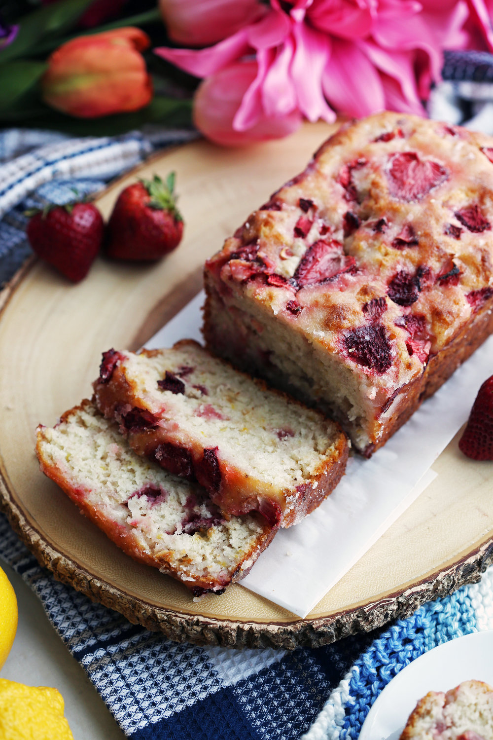 A loaf of Strawberry Lemon Yogurt Quick Bread with two slices cut on a large wooden platter.