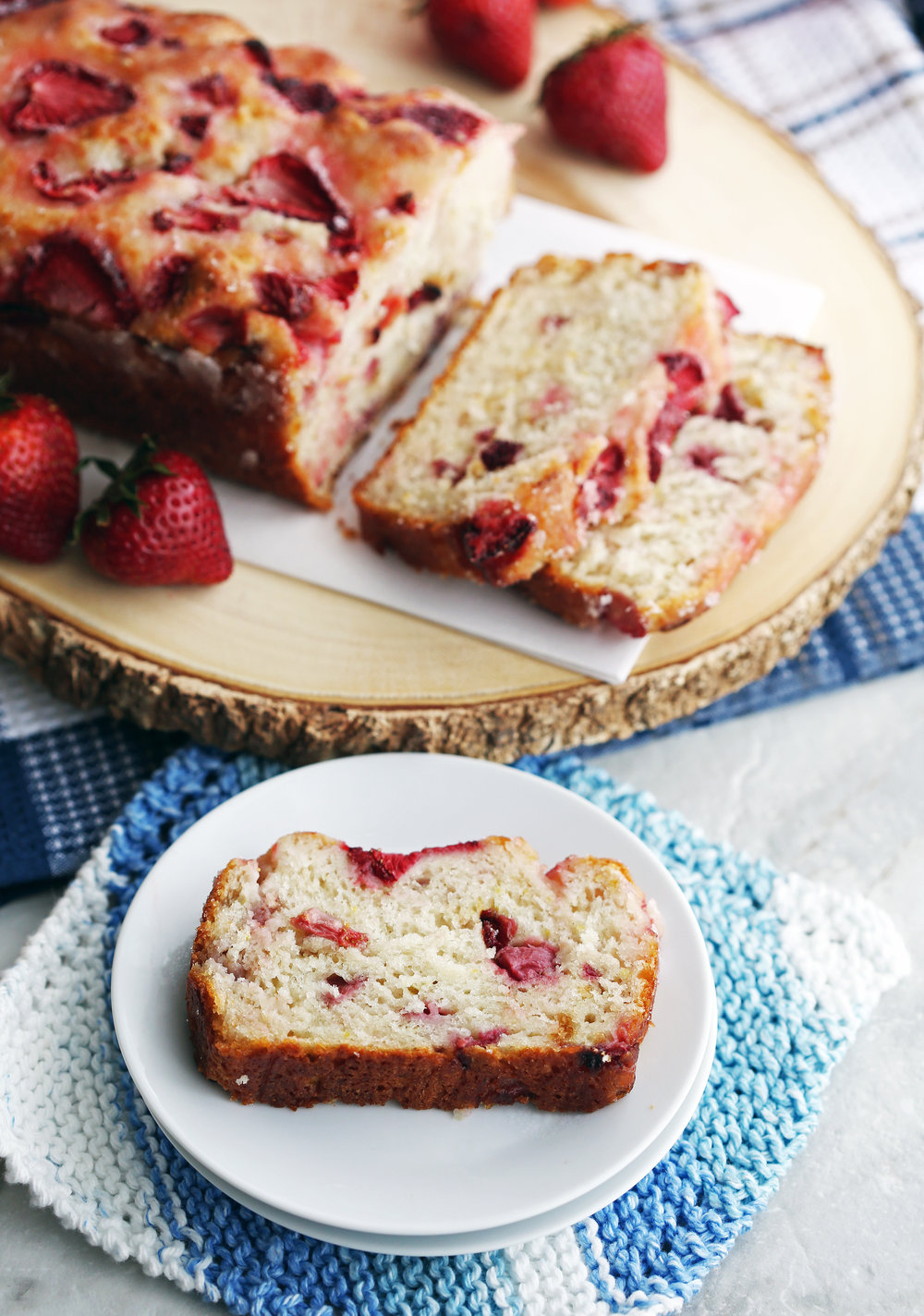 A slice of Strawberry Lemon Yogurt Quick Bread on a small white plate with the loaf in the background.