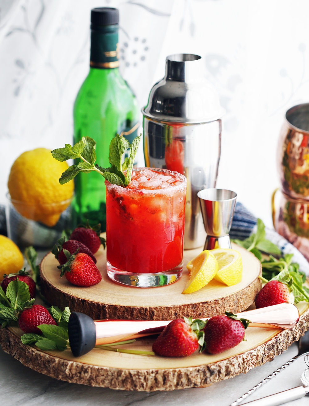 A glass of Mint Strawberry Whisky Smash drink that's sitting on two wooden platters and surrounded by a cocktail set, lemons, and strawberries.