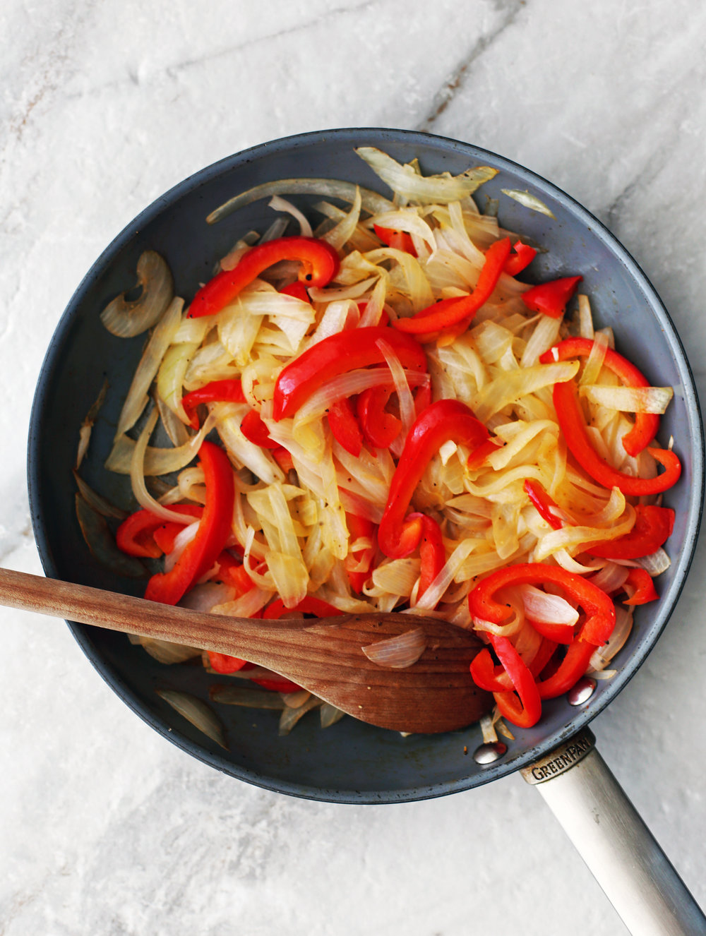 Sauteed sliced onions and peppers in a skillet with a wooden spoon.