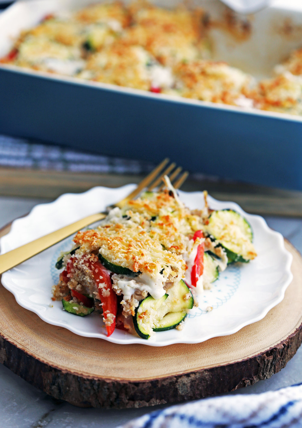 A piece of Zucchini Gratin with Gruyère and Panko Breadcrumbs on a white plate along with a fork.