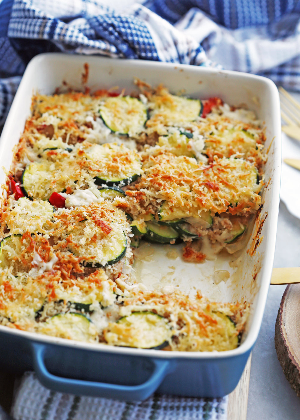 Zucchini Gratin with Gruyère and Panko Breadcrumbs in a blue rectangular casserole dish with one piece of gratin removed.