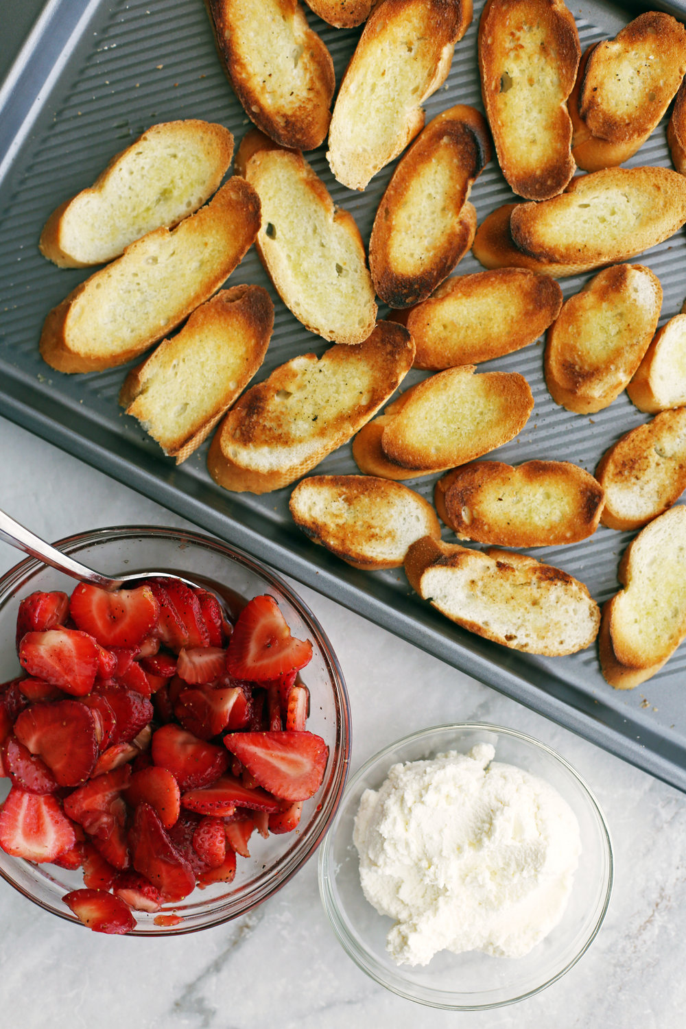 Toasted baguette slices on a baking sheet, a bowl of balsamic strawberries, and a bowl of ricotta.