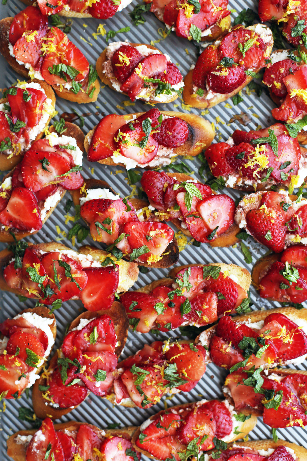 A baking sheet full of Balsamic Strawberry Ricotta Crostini with fresh lemon zest and mint on top.