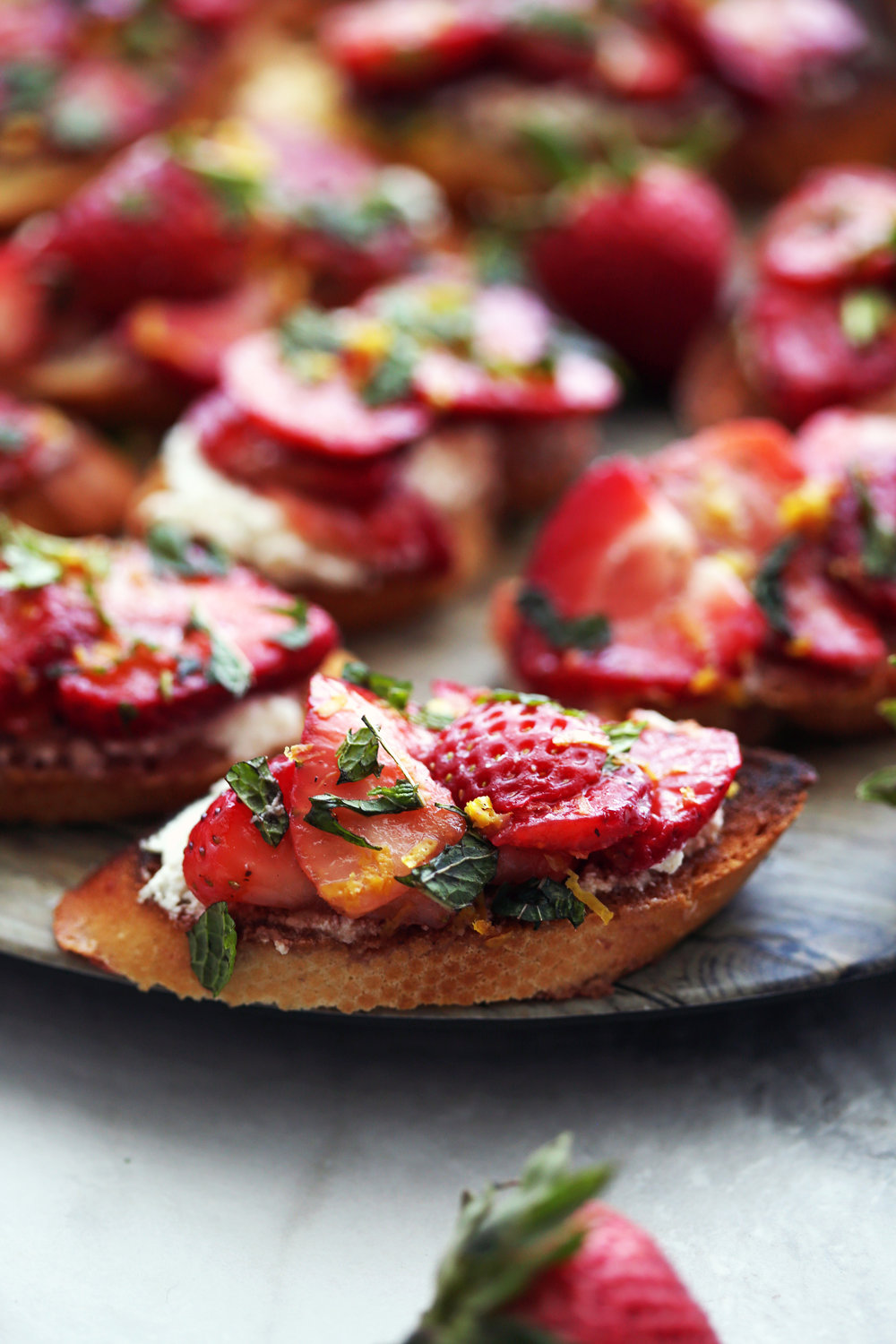 A closeup of a single Balsamic Strawberry Ricotta Crostino with more crostini behind it that's on a large round platter.