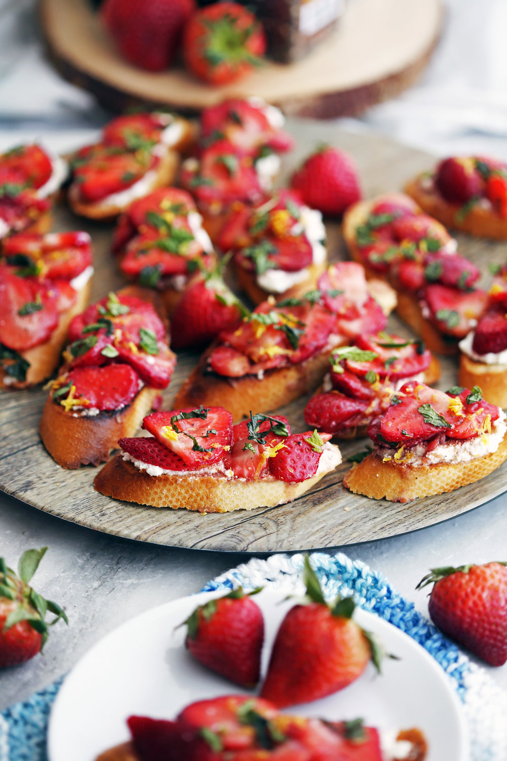 Balsamic Strawberry Ricotta Crostini on a large wooden platter surrounded by fresh strawberries.