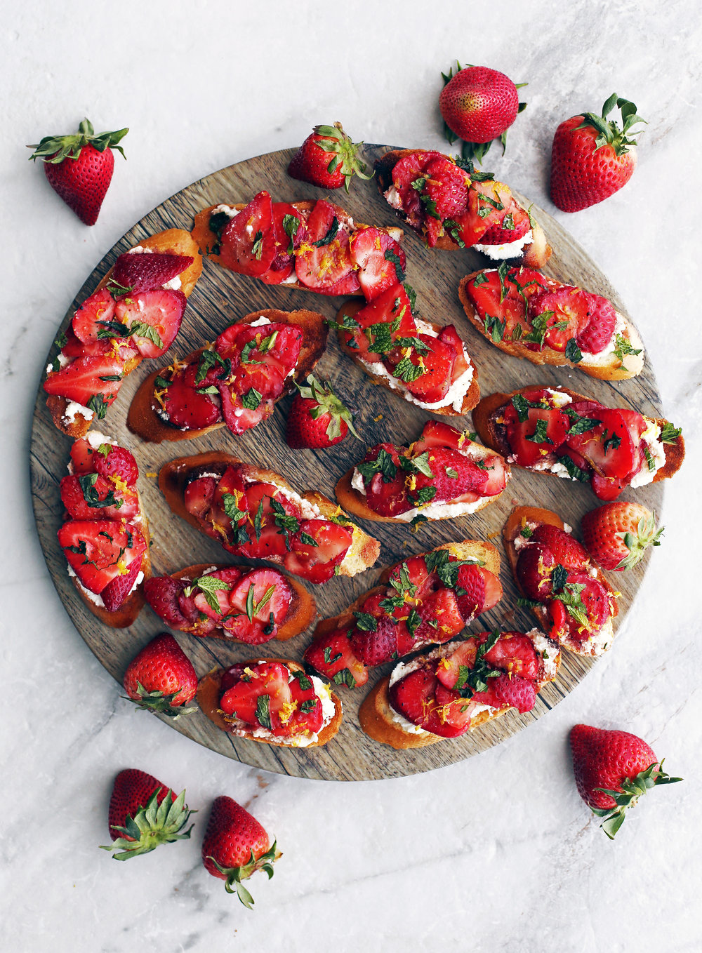 Overhead view of Balsamic Strawberry Ricotta Crostini garnished with mint and lemon zest on a large round platter.