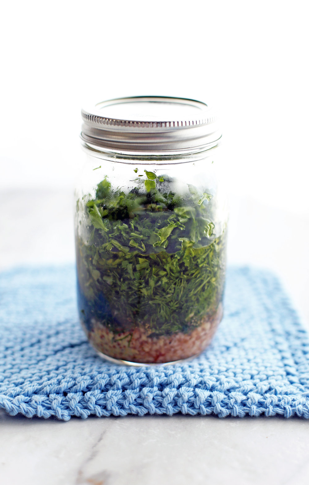 A mason jar full of unshaken olive oil, red wine vinegar, dill, parsley. garlic, dijon mustard, salt, and pepper.