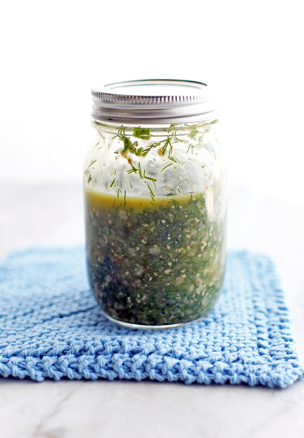 A mason jar containing olive oil, red wine vinegar, dill, parsley. garlic, dijon mustard, salt, and pepper shaken together to form a vinaigrette.