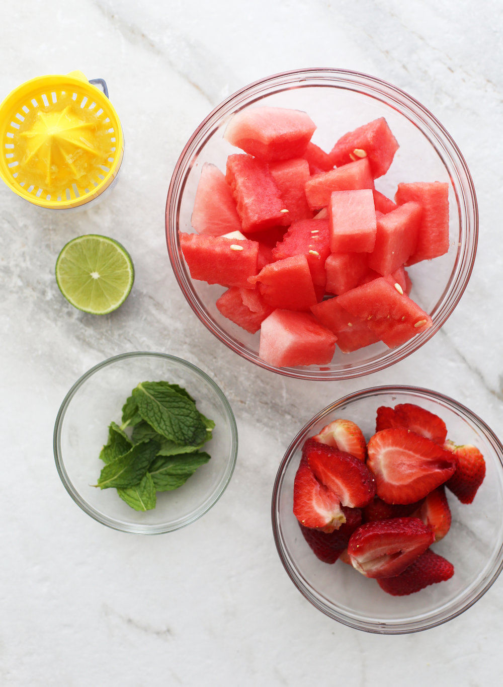 Bowls of strawberries, watermelon, fresh mint, and half a lime.