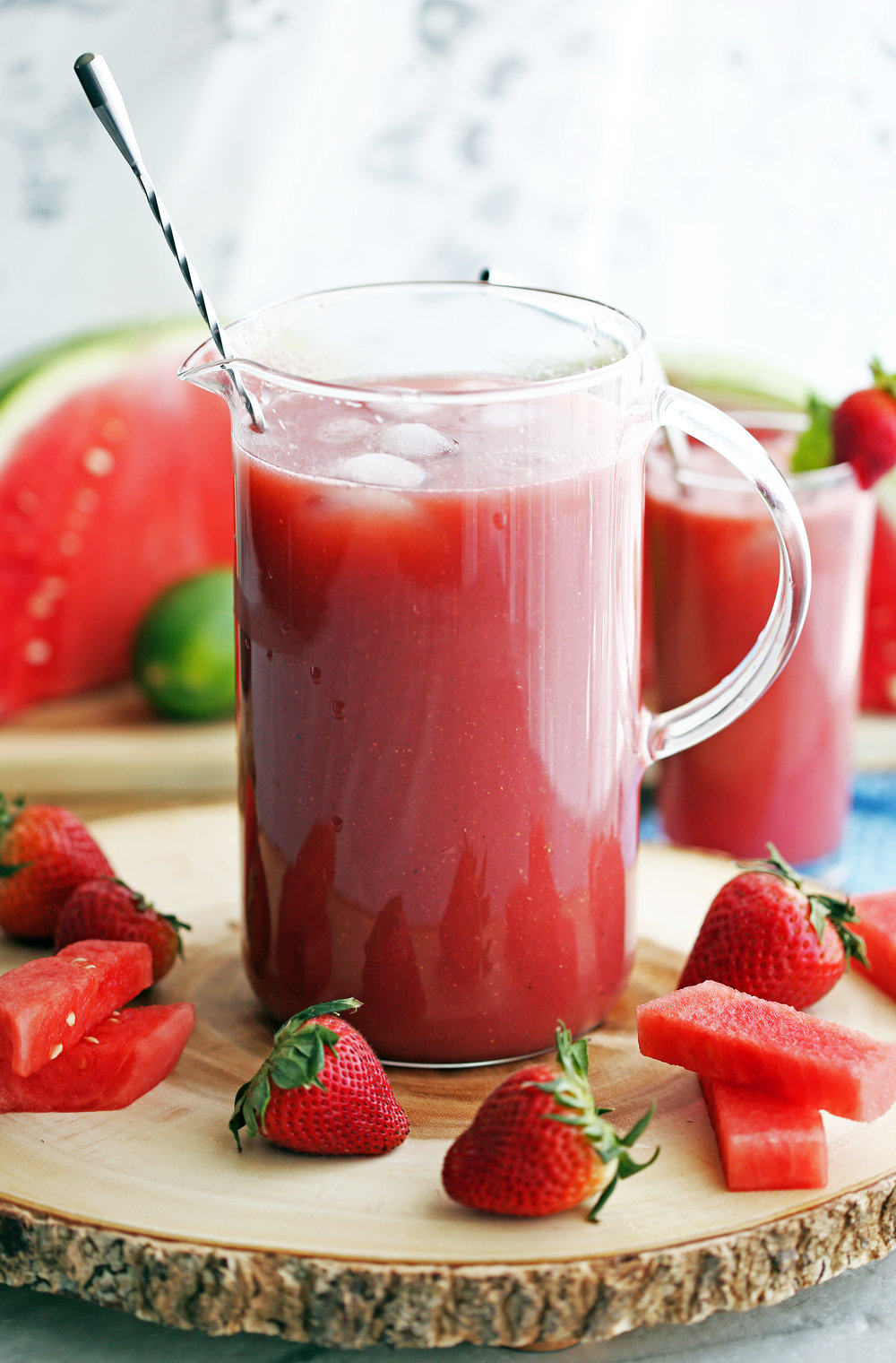 A glass pitcher full of Fresh Watermelon Strawberry Soda that's surrounded by fresh strawberries and watermelon pieces.
