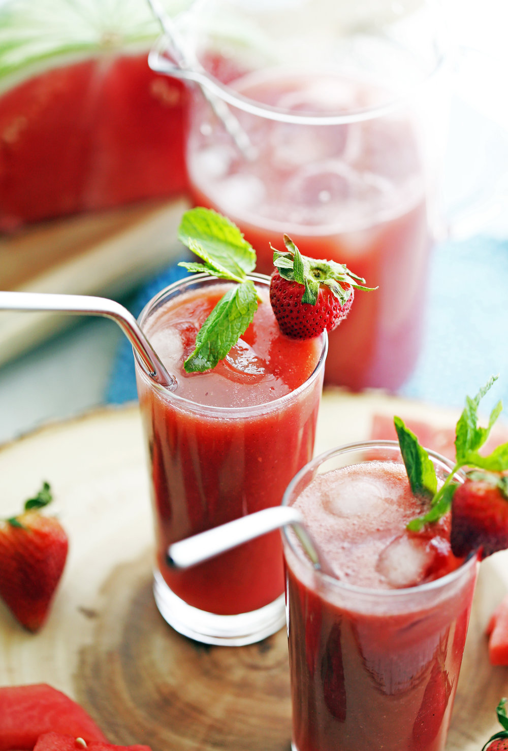 Two tall glasses full of Fresh Watermelon Strawberry Soda with ice and strawberry and mint garnish.