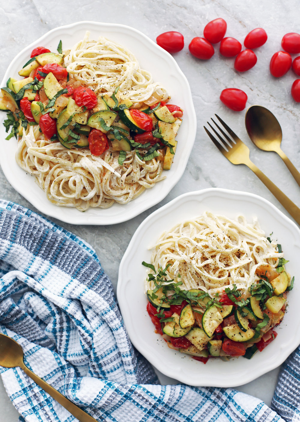 Two white plates containing creamy goat cheese pasta with sauteed zucchini and tomatoes and fresh basil.