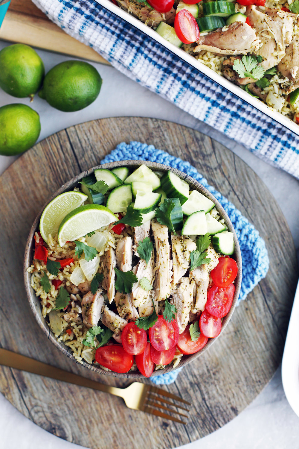 Instant Pot Cilantro Lime Chicken and Rice with tomatoes, cucumbers, and lime wedges in a wooden bowl.