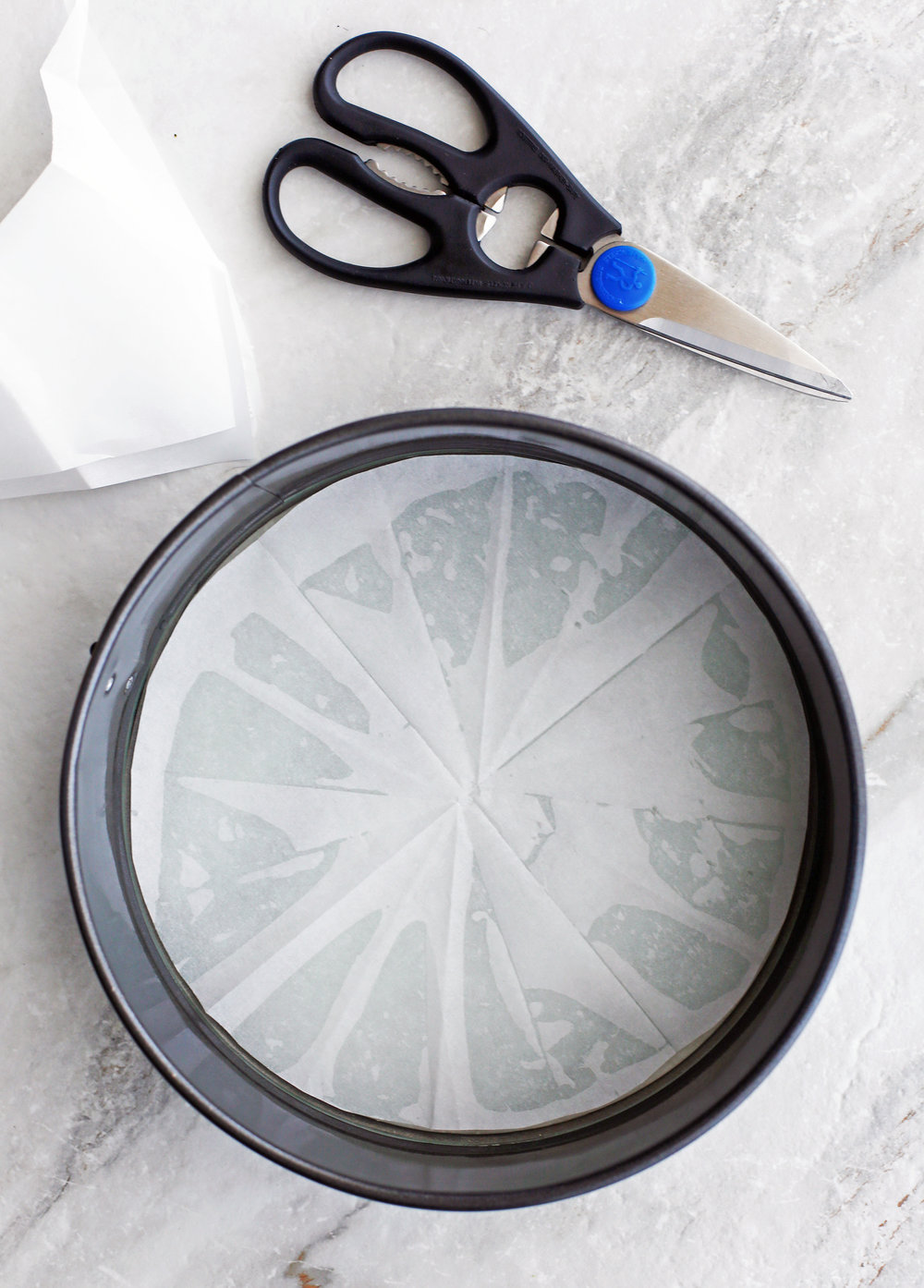 A metal 9-inch round springform pan that's been greased and lined with parchment paper.