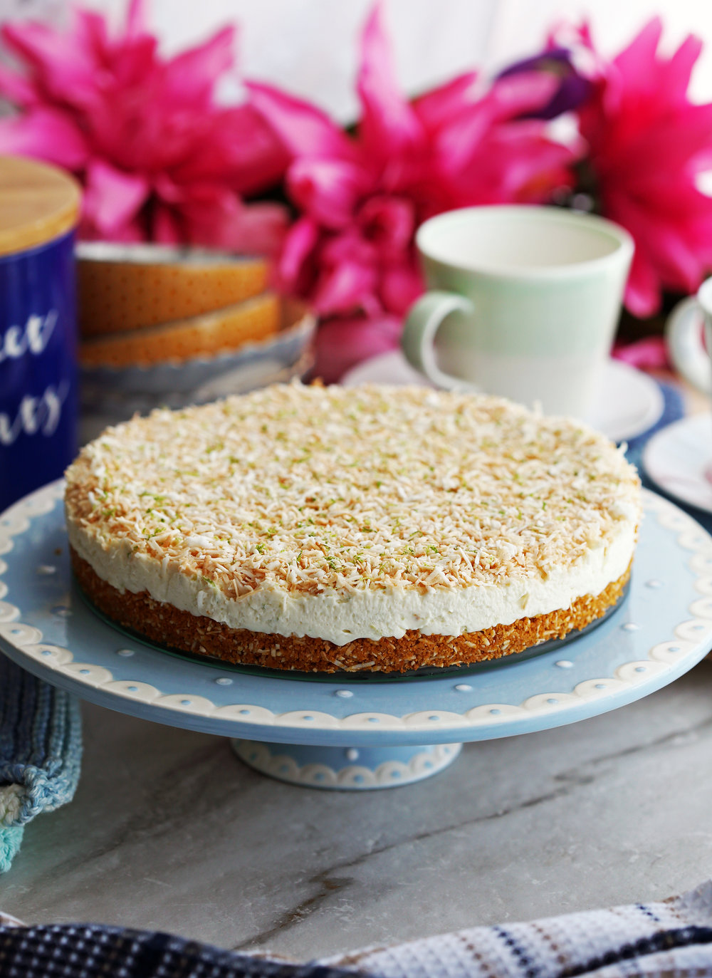 A whole uncut no-bake coconut lime mascarpone cheesecake on a elevated blue cake platter.